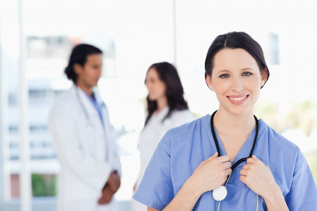 Sonriente médico pasante con el pelo atado de pie delante de su equipo