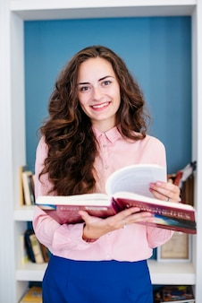 Sonriente morena con libro de texto