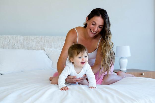 Sonriente morena sentada en una cama con un bebé gateando