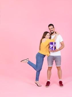 Sonriente mujer abrazando a su novio con caja de regalo contra el fondo rosa