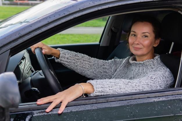 Sonriente mujer adulta conduciendo un coche