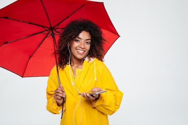 Sonriente mujer africana en gabardina escondiéndose bajo el paraguas y escuchando música
