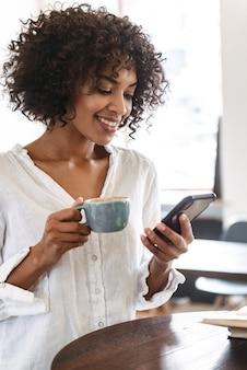 Sonriente mujer africana joven y bonita relajarse en el interior, mediante teléfono móvil