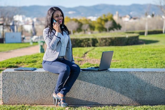 Sonriente mujer afroamericana en un banco usando una computadora portátil y hablando por un teléfono celular en un parque al aire libre