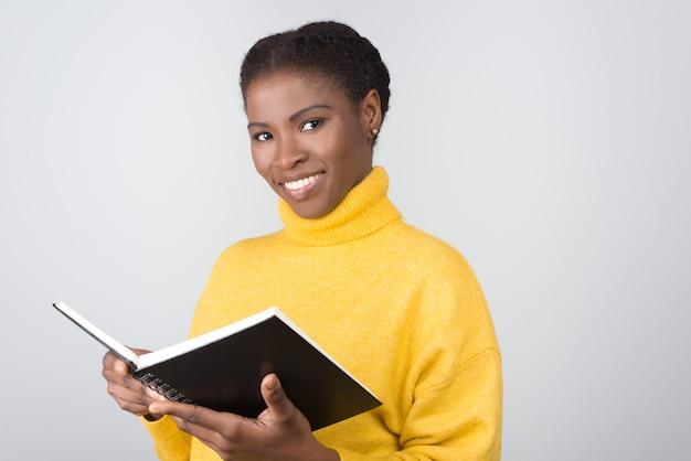 Sonriente mujer afroamericana con bloc de notas