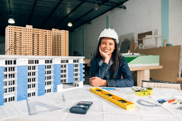 Sonriente mujer afroamericana en casco de seguridad cerca del modelo de edificio