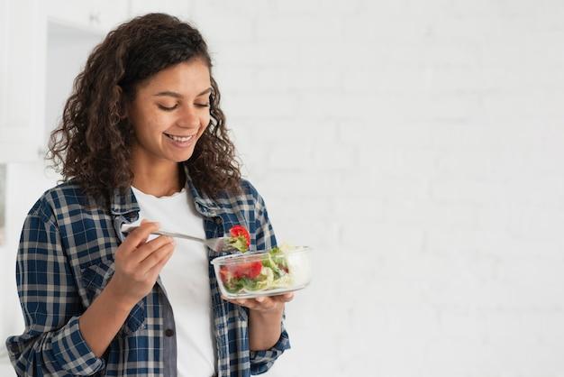 Sonriente mujer afroamericana comiendo ensalada