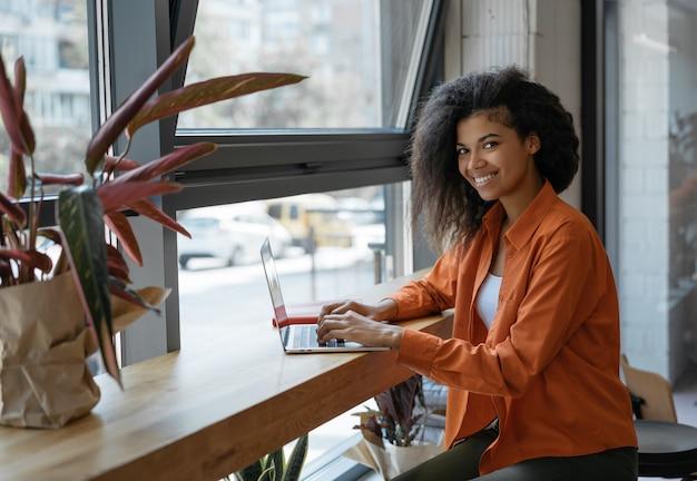 Sonriente mujer afroamericana redactora proyecto de trabajo desde casa, usando una computadora portátil, escribiendo