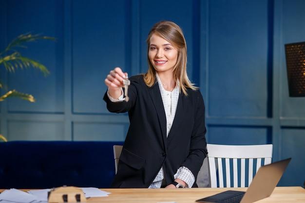 Sonriente mujer agente de bienes raíces da llaves