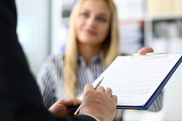 Sonriente mujer agente de bienes raíces que ofrece documento de visitante masculino para firmar