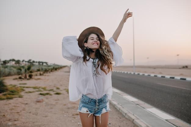 Sonriente mujer alegre de pelo largo con cabello rizado respira un pecho lleno y disfruta de la libertad, de pie junto a la carretera. retrato de mujer joven adorable en blusa blanca y pantalones cortos de mezclilla divirtiéndose afuera