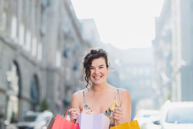 Sonriente mujer amante de las compras con bolsas de papel de colores