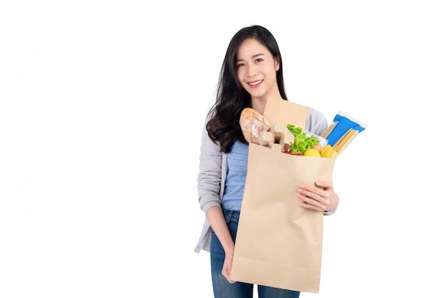 Sonriente mujer asiática con bolsa de papel llena de verduras y comestibles