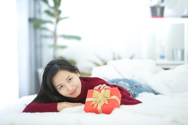 Sonriente mujer asiática espera caja de regalo roja