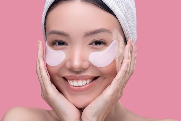 Sonriente mujer asiática con un pañuelo blanco aplicando parches debajo de los ojos