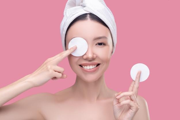 Sonriente mujer asiática con un pañuelo blanco con esponjas para limpiar y cerrar un ojo