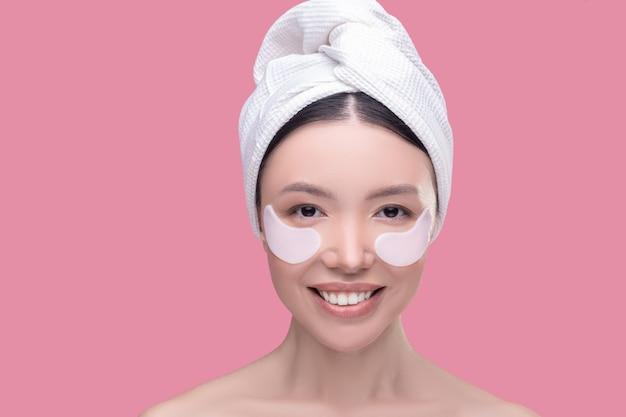 Sonriente mujer asiática en un pañuelo blanco con parches en los ojos que se siente bien