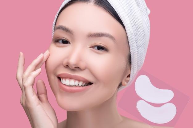 Sonriente mujer asiática en un pañuelo blanco con procedimientos de belleza