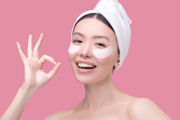 Sonriente mujer asiática en un pañuelo blanco sonriendo y sintiéndose bien