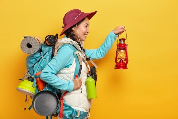 Sonriente mujer asiática sostiene una pequeña lámpara de aceite, va a explorar el lugar en la oscuridad, lleva una mochila con pertenencias personales