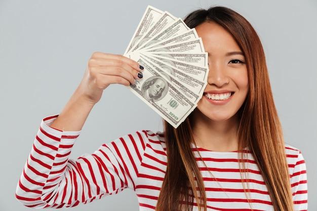 Sonriente mujer asiática en suéter está cubriendo en dinero de la mitad de la cara y mirando a la cámara sobre fondo gris