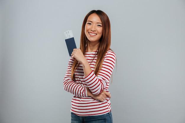 Sonriente mujer asiática en suéter con pasaporte con entradas
