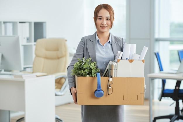 Sonriente mujer asiática en traje de negocios de pie en la oficina con sus pertenencias en caja de cartón