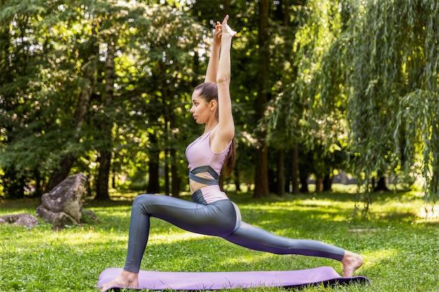 Sonriente mujer atlética está haciendo yoga en medio del parque