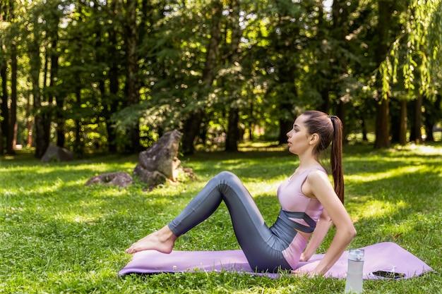 Sonriente mujer atlética está haciendo yoga