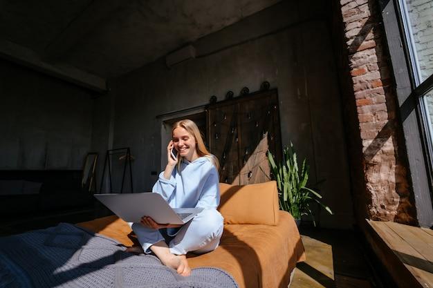 Sonriente mujer atractiva acostada en la cama hablando por teléfono inteligente