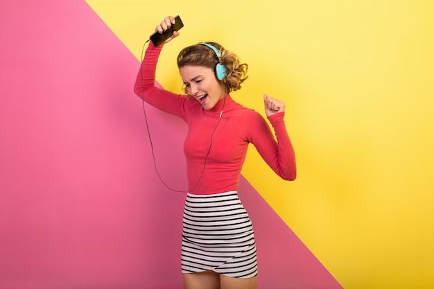 Sonriente mujer atractiva en elegante traje colorido bailando y escuchando música en auriculares