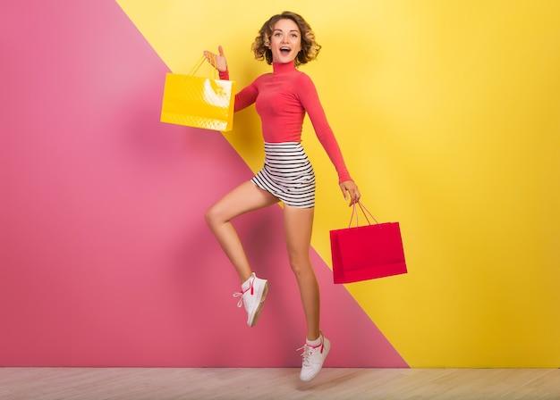 Sonriente mujer atractiva en elegante traje colorido saltando con bolsas de la compra, feliz, fondo amarillo rosa, cuello polo, minifalda rayada, venta, discout, adicta a las compras, tendencia de moda de verano, emocional