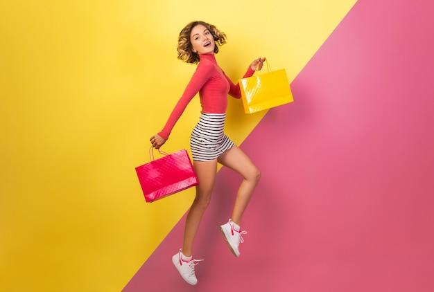 Sonriente mujer atractiva en elegante traje colorido saltando con bolsas de la compra sobre fondo amarillo rosa, cuello polo, minifalda rayada, adicta a las compras en venta, tendencia de moda de verano