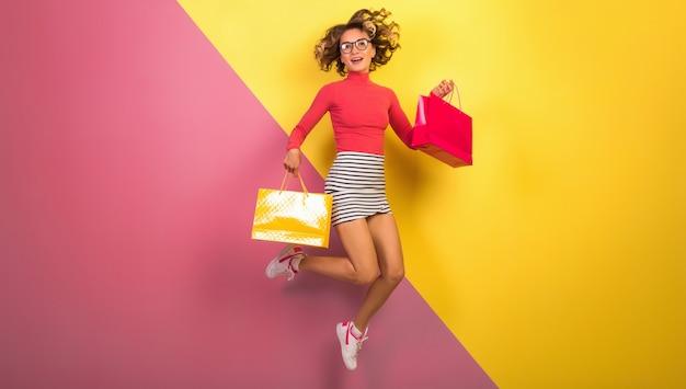 Sonriente mujer atractiva en elegante traje colorido saltando con bolsas de la compra.
