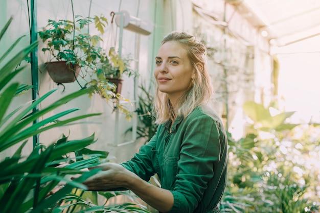 Sonriente mujer atractiva joven que trabaja en el vivero de plantas
