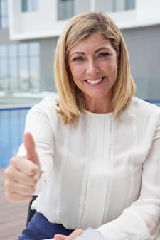 Sonriente mujer atractiva de mediana edad mostrando pulgar arriba al aire libre.