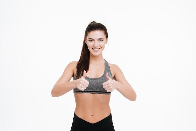 Sonriente mujer atractiva mostrando dos pulgares arriba aislado