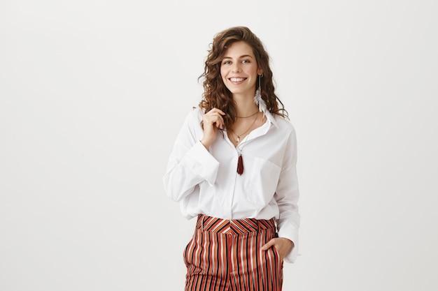 Sonriente mujer atractiva en ropa elegante