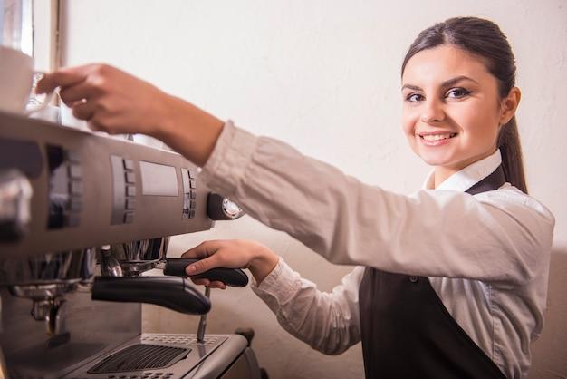Sonriente mujer barista está preparando café en la cafetería.