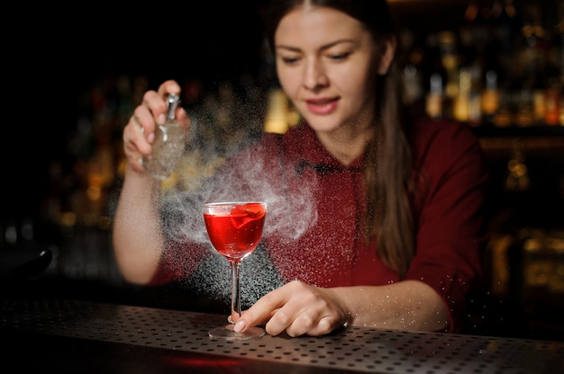 Sonriente mujer barman rociando un vaso de cóctel lleno de sabrosa jeringa aperol cóctel de verano con un whisky pelado