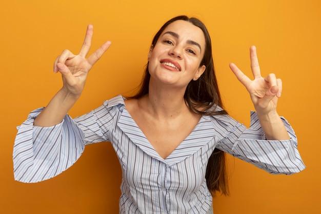 Sonriente mujer bastante caucásica gestos signo de mano de victoria con las dos manos en naranja