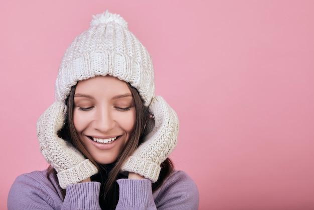 Sonriente mujer de belleza con los ojos cerrados en un sombrero de punto blanco invierno y guantes blancos