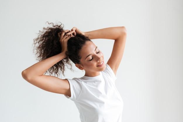 Sonriente mujer bonita con los ojos cerrados jugando con su cabello