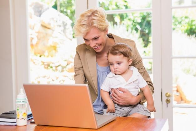 Sonriente mujer bonita rubia usando la computadora portátil con su hijo