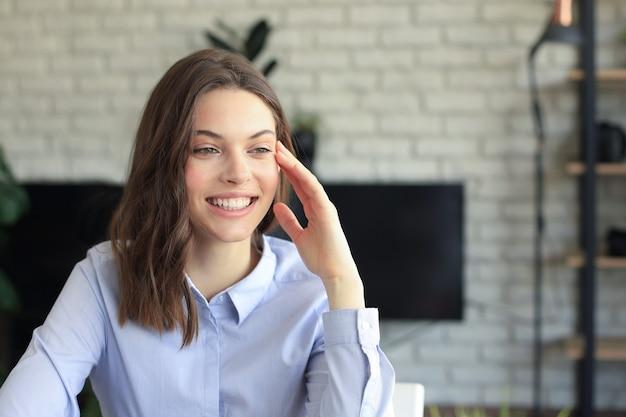 Sonriente mujer bonita sentada a la mesa, mirando la pantalla del portátil. feliz empresario leyendo un mensaje de correo electrónico con buenas noticias, charlando con clientes en línea.