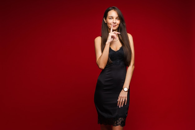 Sonriente mujer bonita con vestido de seda negro y de pie, en rojo .. espacio de copia