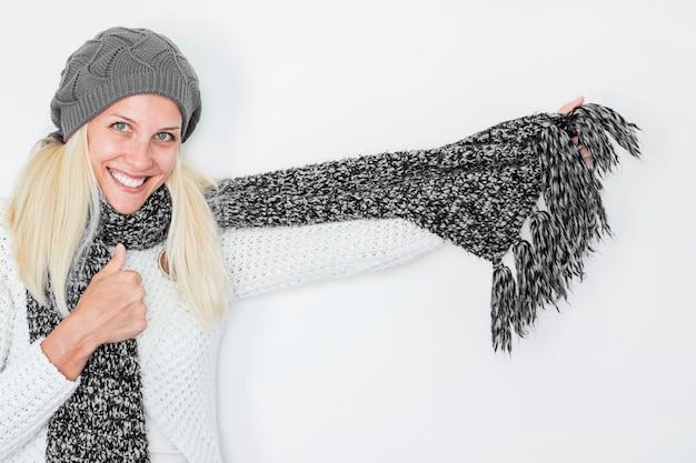 Sonriente mujer en bufanda y sombrero