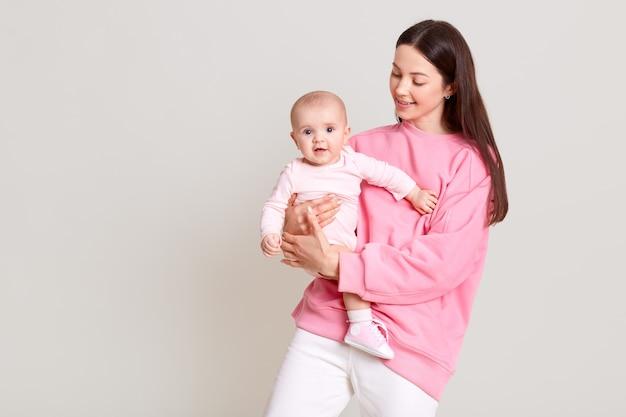 Sonriente mujer de cabello oscuro en ropa casual sosteniendo a la pequeña niña en las manos, mira a su bebé, niño emocionado con traje, posando aislado sobre una pared blanca.