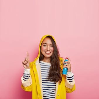 Sonriente mujer de cabello oscuro usa spray para tratar el dolor de garganta, tiene una enfermedad respiratoria estacional, usa un impermeable amarillo con capucha, un suéter a rayas, puntos arriba