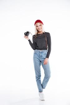 Sonriente mujer casual fotógrafo de pie y sosteniendo la cámara retro